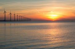 Holandés de las turbinas de viento de la orilla durante una puesta del sol Fotografía de archivo