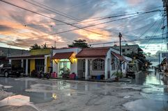 HOLBOX, MEXICO - MAY 25, 2018: Flooded sand roads in the main square of Isla Holbox with tourists and Caribbean houses and shops d stock photo