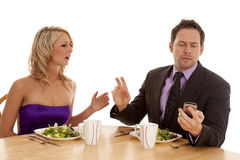 Hold on. A men telling his date to hold on while he checks his phone for a text message Royalty Free Stock Photo