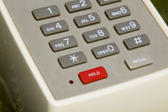 Hold. Partial view of retro office phone with focus on hold button Stock Photos
