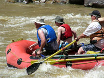 Hold On. River rafters entering rough water in a mountain river Royalty Free Stock Image