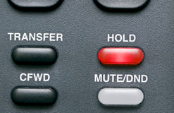 On Hold. Macro shot of a telephone's feature buttons with the hold button red and activated Stock Photography