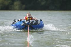 Hold On. Girl water tubing on a lake Royalty Free Stock Photo