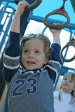 Hold On. 4 year  old boy holding on to the rings Royalty Free Stock Photo