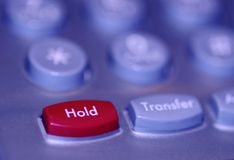 On hold. Close up of a red hold button on an office phone royalty free stock photography