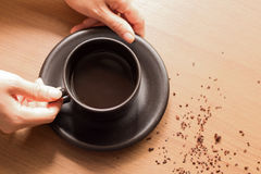 Hold the black coffee in brown cup and roasted coffee on wooden Stock Image