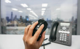 Hold computer mouse in hand. With IP phone background Stock Images