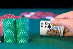 Hold'em Poker Ace King. A hold'em poker player revealing his hand, Ace King of spades (big slick suited), with multiple stacks of chips Stock Images