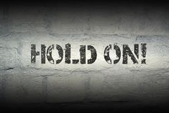 Hold on gr. Hold on exclamation stencil print on the grunge white brick wall Royalty Free Stock Photography