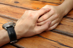 Hold the hands. On the wooden background Stock Photos