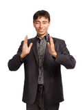 Hold in hands. Young businessman in dark grey coat and steel-blue shirt stands and poses like holding something in hands isolated on white background Royalty Free Stock Photos