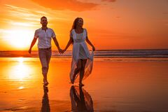 Hold hands with your loved one. Romantic walk along the coast at the sunset.