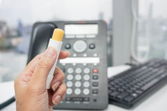 Hold a lip balm. Hold a yellow lip balm with office background Stock Image