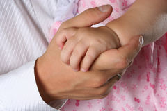 Hold love. The hand of the father holds a hand of the child Stock Photos