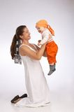Hold me high. Mother on her knees holding her baby boy up high stock image