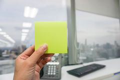 Hold a mockup green postit. With office suppliers background Stock Photo