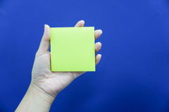 Hold mockup postit in hand. With blue background Royalty Free Stock Image