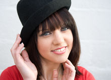 Hold onto your hat. An image of a girl  keeping tight hold of her black hat on a windy day Royalty Free Stock Images