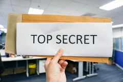 Hold a paper of top secret. With office background Stock Photo