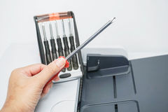 Hold a screwdriver with red handle for printer repair. Hold a screwdriver for printer repair Stock Image