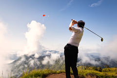 Hold 19th. Competition in business concept: Young asian businessman hit golf ball to flag on the cloud in the sky stock photos