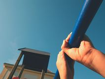 Hold on bars at playground. Kid is holding blue steel bar above head Royalty Free Stock Photography