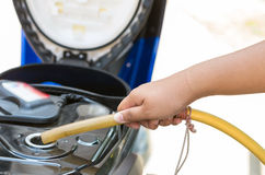 Hold traditional rubber tube to add fuel in motorcycle Royalty Free Stock Photography