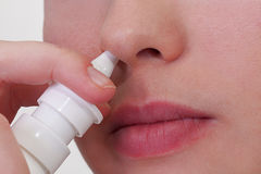 Hold your nose clean. Close-up of unrecognizable woman who about to use nasal spray Stock Images