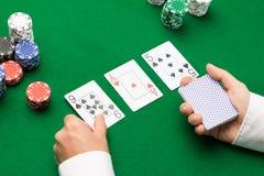Holdem återförsäljare med att spela kort och kasinochiper Arkivbild