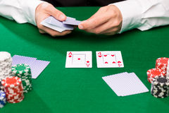 Holdem dealer with playing cards and casino chips. Casino, gambling, poker, people and entertainment concept - close up of holdem dealer with playing cards and Stock Image