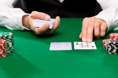 Holdem dealer with playing cards and casino chips. Casino, gambling, poker, people and entertainment concept - close up of holdem dealer with playing cards and Stock Photo