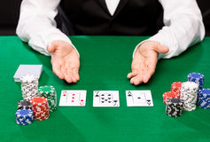 Holdem dealer with playing cards and casino chips. Casino, gambling, poker, people and entertainment concept - close up of holdem dealer with playing cards and Stock Images