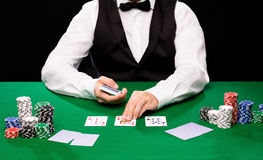 Holdem dealer with playing cards and casino chips. Casino, gambling, poker, people and entertainment concept - close up of holdem dealer with playing cards and Royalty Free Stock Image