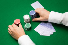 Holdem dealer with playing cards and casino chips. Casino, gambling, poker, people and entertainment concept - close up of holdem dealer with playing cards and Royalty Free Stock Photo