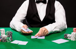 Holdem dealer with playing cards and casino chips. Casino, gambling, poker, people and entertainment concept - close up of holdem dealer with playing cards and Royalty Free Stock Images