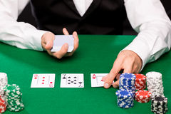 Holdem dealer with playing cards and casino chips. Casino, gambling, poker, people and entertainment concept - close up of holdem dealer with playing cards and Stock Photos