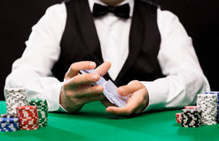 Holdem dealer with playing cards and casino chips. Casino, gambling, poker, people and entertainment concept - close up of holdem dealer shuffling playing cards Royalty Free Stock Photography