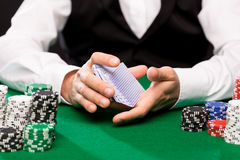 Holdem dealer with playing cards and casino chips. Casino, gambling, poker, people and entertainment concept - close up of holdem dealer shuffling playing cards Royalty Free Stock Photos
