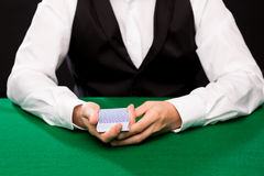 Holdem dealer with playing cards. Casino, gambling, poker, people and entertainment concept - close up of holdem dealer with playing cards Royalty Free Stock Images