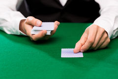 Holdem dealer with playing cards. Casino, gambling, poker, people and entertainment concept - close up of holdem dealer with playing cards Stock Photo