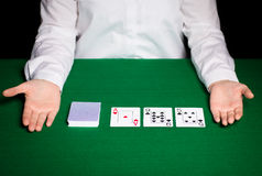 Holdem dealer with playing cards. Casino, gambling, poker, people and entertainment concept - close up of holdem dealer with playing cards Royalty Free Stock Image