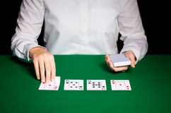 Holdem dealer with playing cards. Casino, gambling, poker, people and entertainment concept - close up of holdem dealer with playing cards Stock Images