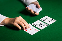 Holdem dealer with playing cards. Casino, gambling, poker, people and entertainment concept - close up of holdem dealer with playing cards Royalty Free Stock Photos