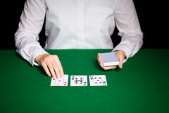 Holdem dealer with playing cards. Casino, gambling, poker, people and entertainment concept - close up of holdem dealer with playing cards Royalty Free Stock Photography