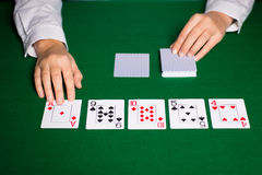 Holdem dealer with playing cards. Casino, gambling, poker, people and entertainment concept - close up of holdem dealer hands with playing cards Stock Image