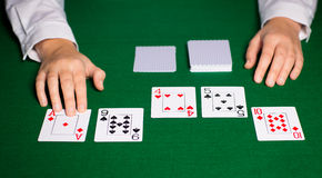 Holdem dealer with playing cards. Casino, gambling, poker, people and entertainment concept - close up of holdem dealer hands with playing cards Stock Photos