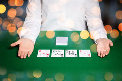 Holdem dealer with playing cards over lights. Casino, gambling, poker, people and entertainment concept - close up of holdem dealer with playing cards on green Royalty Free Stock Photography