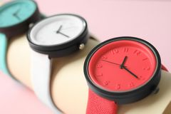 Holder with collection of stylish wrist watches on color background. Fashion accessory stock images