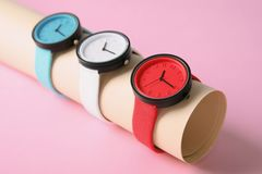 Holder with collection of stylish wrist watches on color background. Fashion accessory stock image