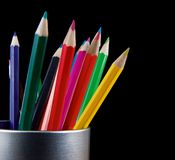 Holder full of colorful pencils isolated on black Stock Images